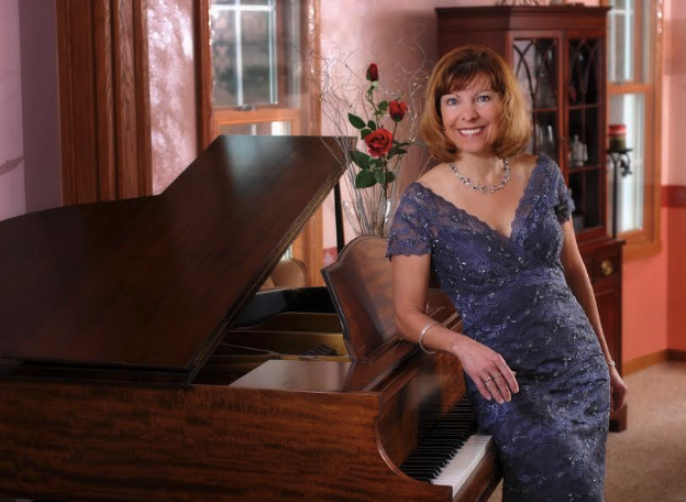 Carla McKrell leaning against piano
